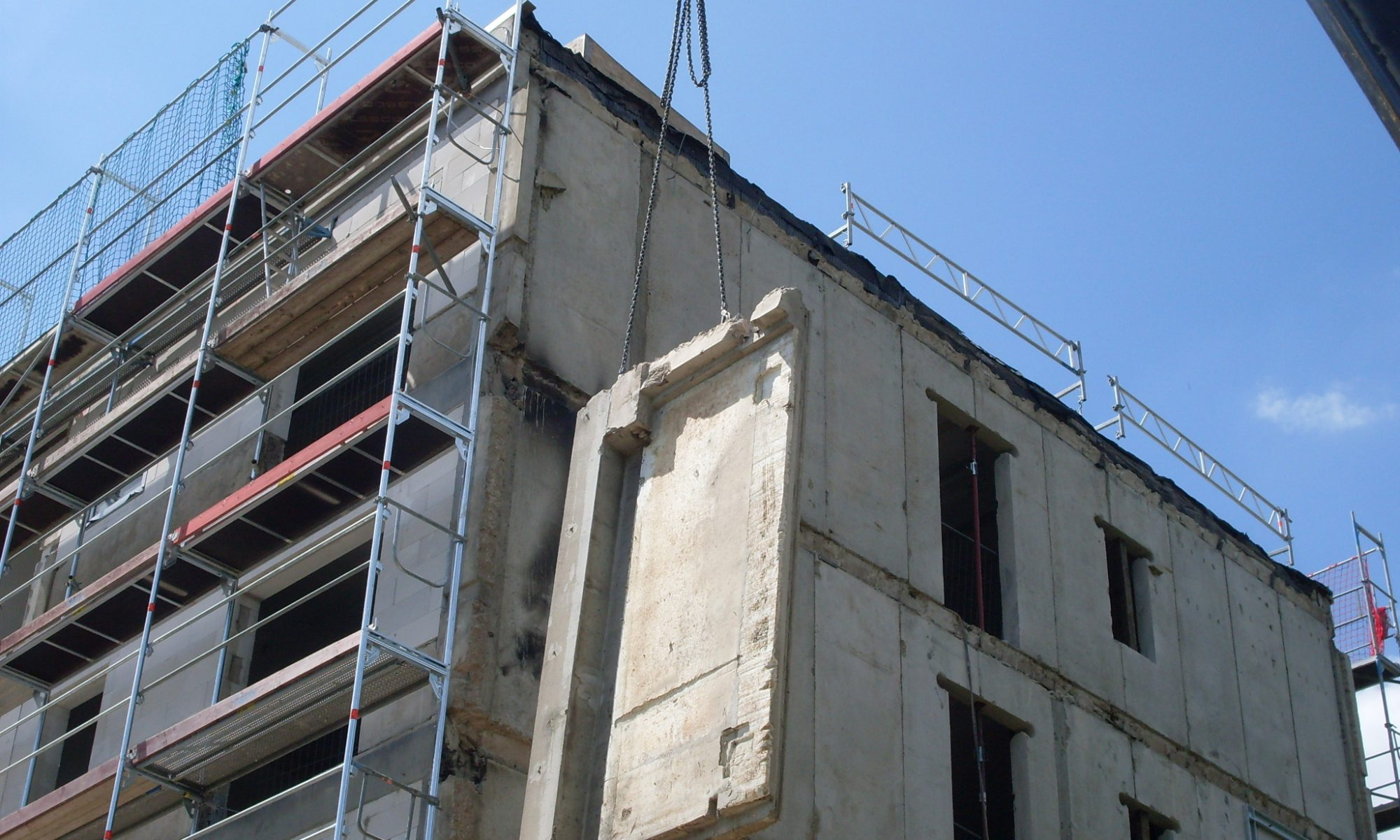 Die Wettetschale aus Beton von einer Plattenbauschule hängt mit Ketten am Kran